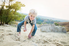 Blond little boy playing on sand beach. Royalty Free Stock Images