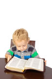 Blond little boy reading the bible. Sitting at the big table Stock Image