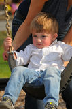 Blond little boy swinging on a swing Stock Images