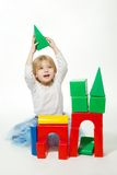 Blond little girl building house Royalty Free Stock Photography