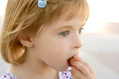 Blond little girl closeup portrait eating biscuit. Blond little girl macro closeup portrait eating biscuit Royalty Free Stock Photos