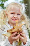 Blond little girl collecting autmn leaves royalty free stock images