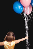 Blond little girl with colorful balloons, rear view Royalty Free Stock Photo