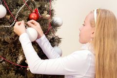 Blond little girl decorates a Christmas tree. At home Stock Photos