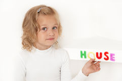 Blond little girl dressed in white. Blond little girl  dressed in white stuck word  house of colorful letters  on the shelf and looking directly at the camera Royalty Free Stock Images