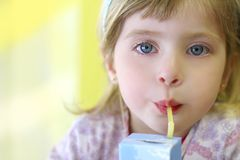 Blond little girl drinking straw tetra brick Royalty Free Stock Photos