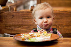 Blond little girl in front of a big plate Royalty Free Stock Photos