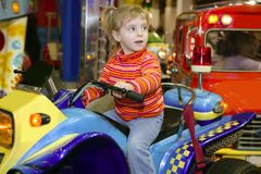 Blond little girl in funfair fairground attraction. Car Royalty Free Stock Photo