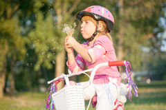 Blond little girl on her bike blowing a dandelion Stock Images