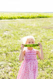 Blond little girl holds a watermelon slice in his hands. The girl is eating a watermelon Royalty Free Stock Image