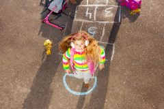 Blond little girl jumps on hopscotch Royalty Free Stock Photography