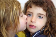 Blond little girl kissing her daughter blue eyes Stock Images