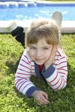 Blond little girl laying on pool grass posing. Blond little girl laying on pool grass Royalty Free Stock Photo