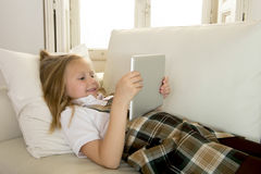 Blond little girl lying on home sofa couch using internet app on digital tablet pad on digital tablet pad Royalty Free Stock Photography