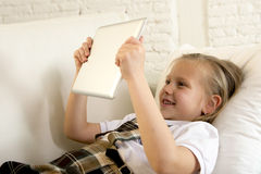 Blond little girl lying on home sofa couch using internet app on digital tablet pad on digital tablet pad Royalty Free Stock Photos