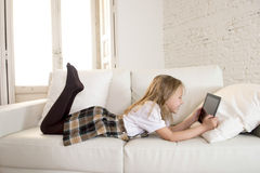 Blond little girl lying on home sofa couch using internet app on digital tablet pad on digital tablet pad Stock Images