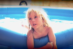 Blond little girl playing in the pool. Little girl playing in a blue swimming pool Stock Photo