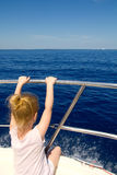 Blond little girl rear view sailing in boat Royalty Free Stock Photos