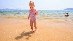 Blond Little Girl Runs with Ball along Sand Beach by Shallow Sea stock video footage