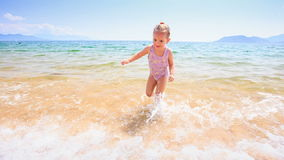 Blond Little Girl Runs out of Sea to Golden Sand Beach. Blond little girl with pigtail runs out of transparent shallow azure sea to sand beach against blue sky stock footage