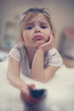 Blond little girl. Sad little girl watching TV lying on floor with remote control in hand Stock Photos