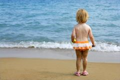 Blond little girl with sandy legs on the beach Stock Image