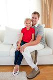 Blond little girl sitting on sofa with her father Stock Image