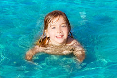Blond little girl swimming in turquoise beach Royalty Free Stock Photos