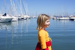 Blond little girl walking blue marina Stock Photography
