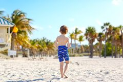 Blond little kid boy having fun on Miami beach, Key Biscayne. Happy healthy cute child playing with sand and running. Near ocean. Palms, security house and stock image