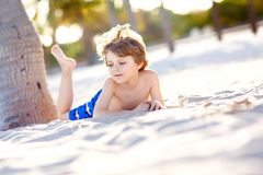 Blond little kid boy having fun on Miami beach, Key Biscayne. Happy healthy cute child playing with sand and running. Near ocean. Palms, security house and stock photos