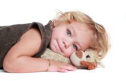 blond lockig flicka som kramar toyen Arkivbilder