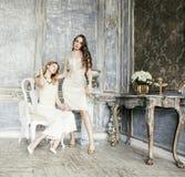 Blond lockig frisyrflicka för nätt tvilling- syster två i lyxig husinre tillsammans, rikt ungdomarbegrepp royaltyfria foton