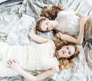 Blond lockig frisyrflicka för nätt tvilling- syster två i lyxig husinre tillsammans, rikt ungdomarbegrepp arkivbilder