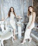 Blond lockig frisyrflicka för nätt tvilling- syster två i lyxig husinre tillsammans, rikt ungdomarbegrepp arkivbild