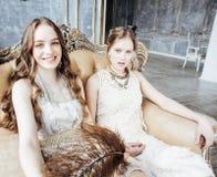 Blond lockig frisyrflicka för nätt tvilling- syster två i lyxig husinre tillsammans, rikt ungdomarbegrepp royaltyfri foto
