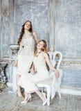 Blond lockig frisyrflicka för nätt tvilling- syster två i lyxig husinre tillsammans, rikt ungdomarbegrepp fotografering för bildbyråer