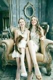 Blond lockig frisyrflicka f?r n?tt tvilling- syster tv? i lyxig husinre tillsammans, rikt ungdomarbegrepp arkivfoto