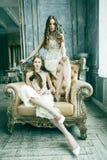 Blond lockig frisyrflicka f?r n?tt tvilling- syster tv? i lyxig husinre tillsammans, rikt ungdomarbegrepp royaltyfria foton