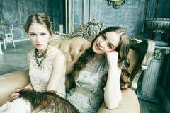 Blond lockig frisyrflicka f?r n?tt tvilling- syster tv? i lyxig husinre tillsammans, rikt ungdomarbegrepp arkivbild