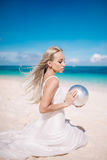 Blond long hair bride in a long white dress sitting on the white sand beach with pearl. stock photo