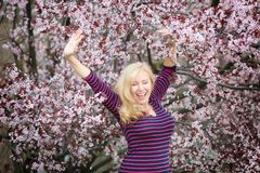 Blond long hair Caucasian woman happy and laughing near blossoming tree Royalty Free Stock Images