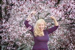 Blond long hair Caucasian woman happy and laughing near blossoming tree Stock Photo