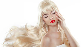 Blond long hair. Sensual woman with red lips. Professional makeu. P. Blowing wavy hairstyle Stock Images