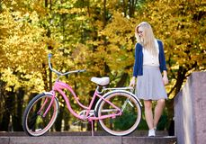 Blond long-haired attractive girl on pink lady bicycle in sunny autumn park on trees background. Young active blond long-haired woman in skirt and blouse royalty free stock photo