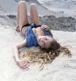 Blond long-haired girl lying on sand and looking at camera Royalty Free Stock Image
