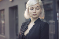 Blond lovely model in sunset light outdoors closeup portrait in black suit and with ear tunnels. no makeup perfect skin. Stock Photo
