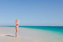 Blond lycklig kvinna som poserar paradisstranden Arkivfoto
