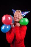 blond lycklig stående för attraktiva ballonger Arkivfoto