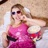 Blond młoda kobieta kłama w łóżku z TV pilot do tv w ręki dopatrywania filmu w 3D szkłach i łasowanie popkornie w kolor piżamach Zdjęcie Royalty Free